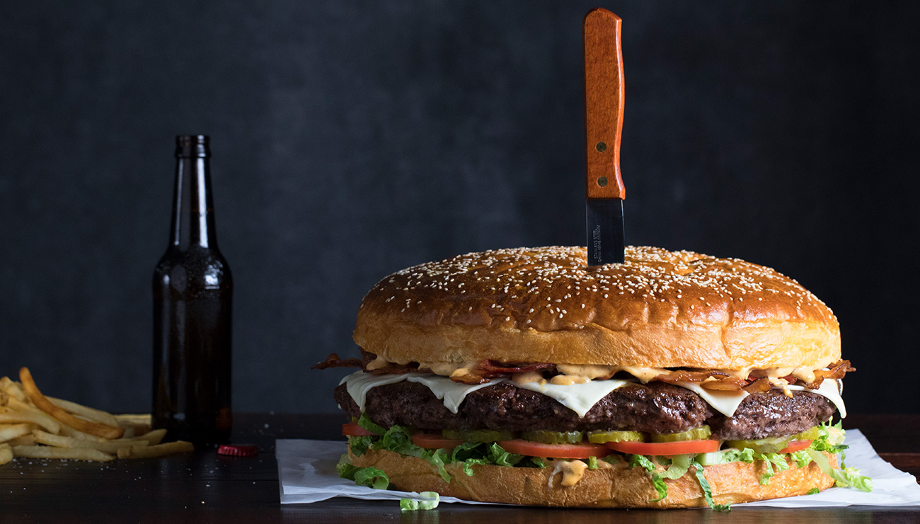 Behemoth Burger with Knife, Beer Bottle and Fries to the Side