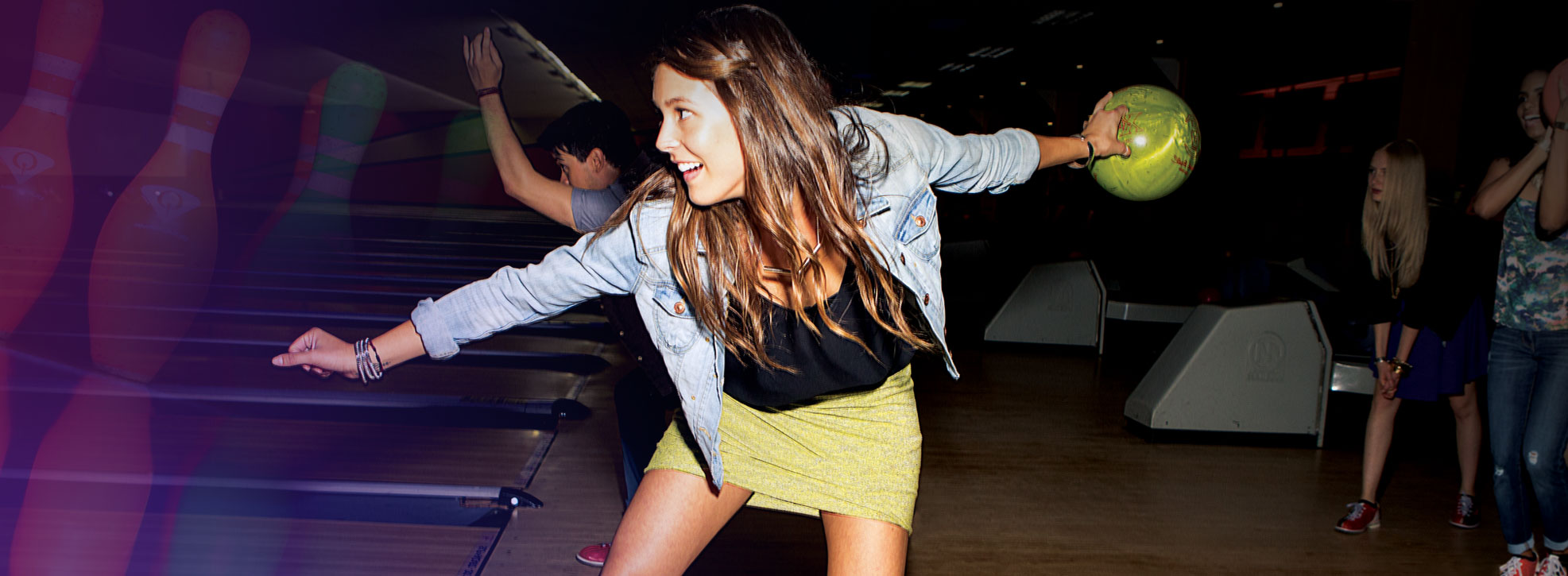 Action shot of young woman bowling