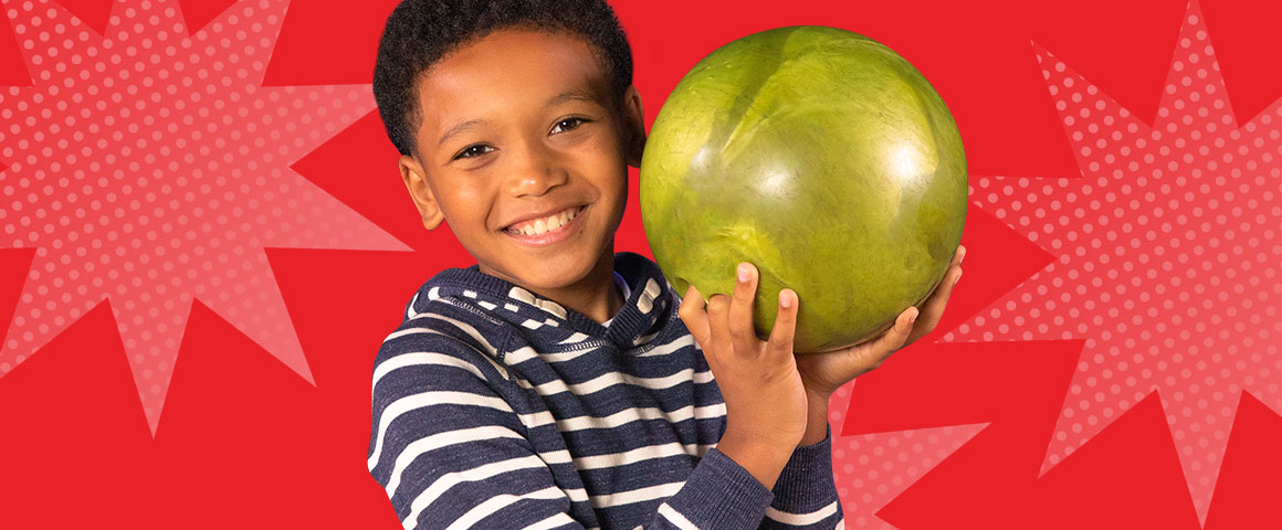 kid holding a bowling bowl and smiling
