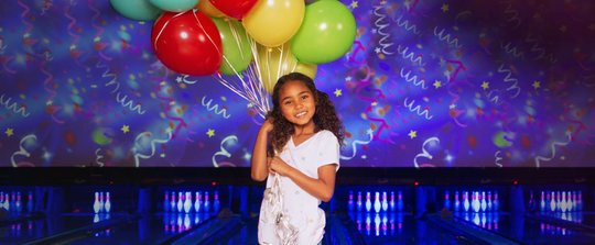 girl holding balloons in front of bowling lanes
