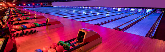 rows of neon light bowling lanes and bowling balls in racks