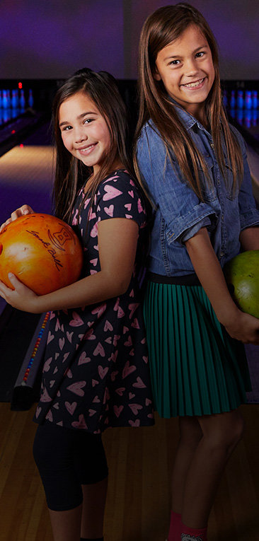 Two young girls smiling and holding bowling balls