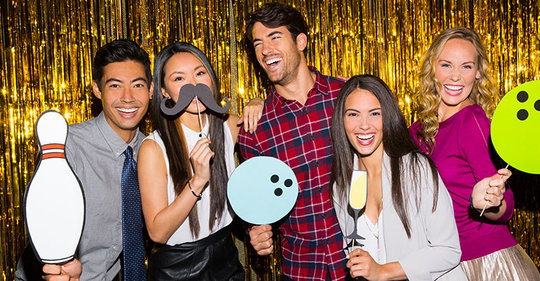 Friends posing in front of gold back drop with photo booth props