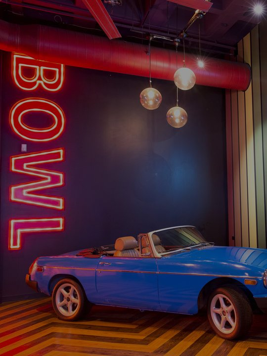 blue vintage convertible car next to neon BOWL sign