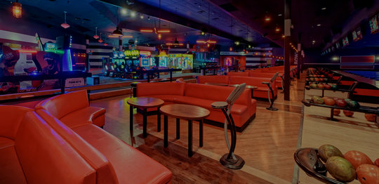 Bowling lanes with red plush couches and arcade in background
