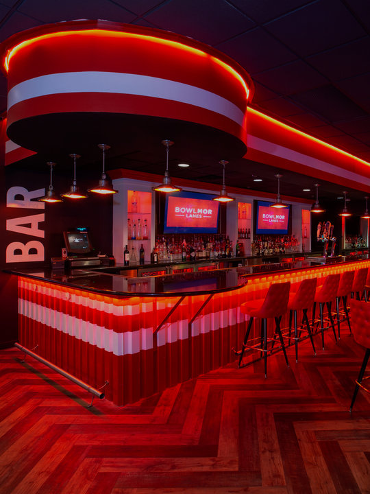 bar area with neon lighting and stools