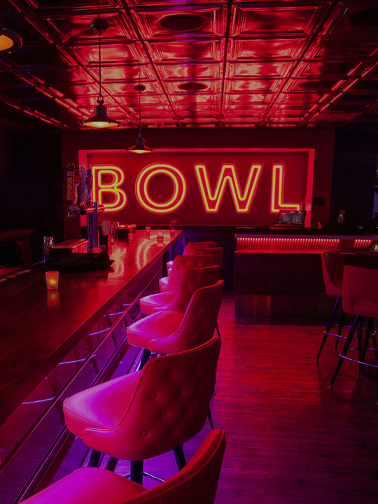 bar area with neon BOWL sign on wall