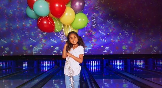 little girl holding balloons standing in front of lanes