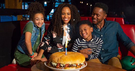family sitting in front of a gigantic burger