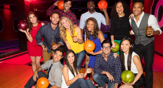 a group of bowlers holding bowling balls, laughing with drinks