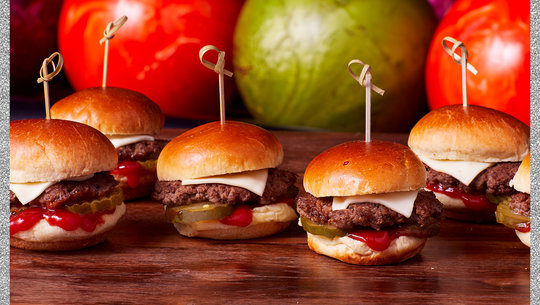 cheese burger sliders in a row with bowling balls in the background
