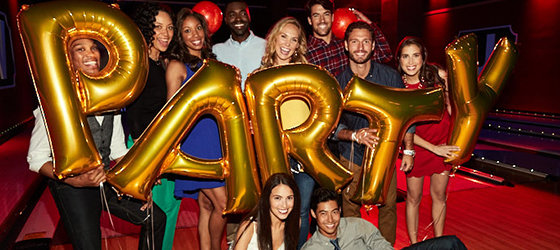 Group of young adults smiling and holding gold balloons that read 'PARTY'