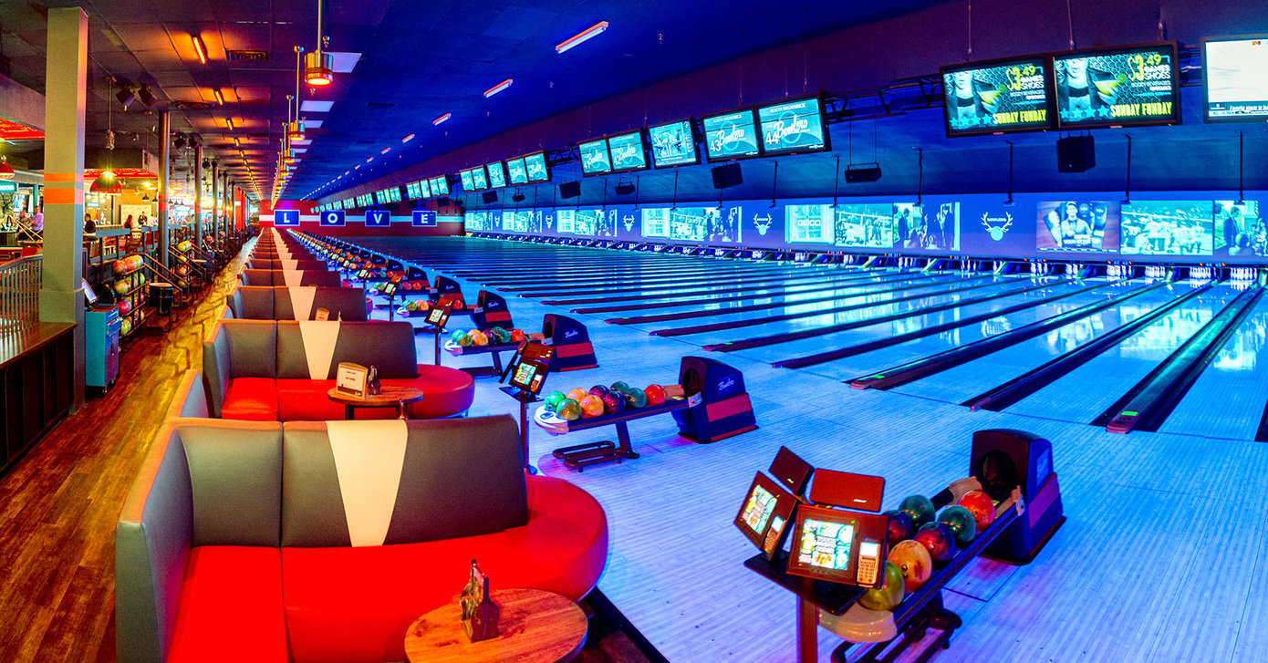 Wide angle shot of a bowling alley with neon lights