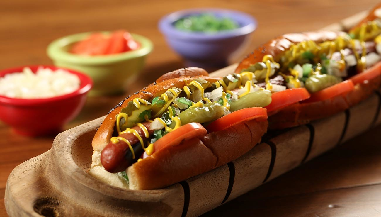 Extra long hot dog covered with toppings, and three bowls of toppings in background.