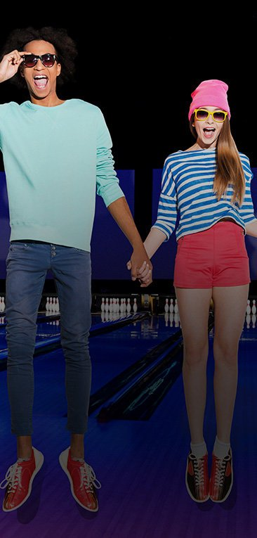 Two teens jumping in front of bowling lanes