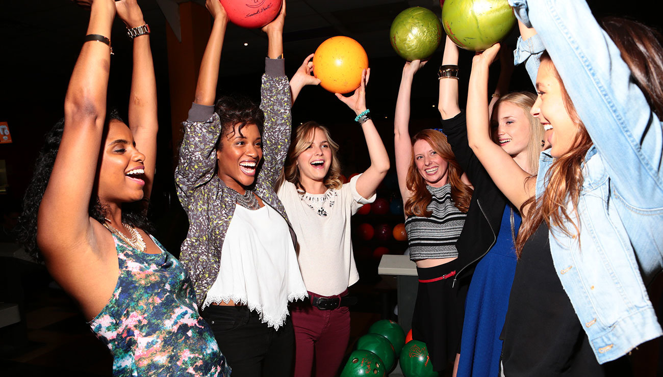 girls holding up bowling balls over their heads