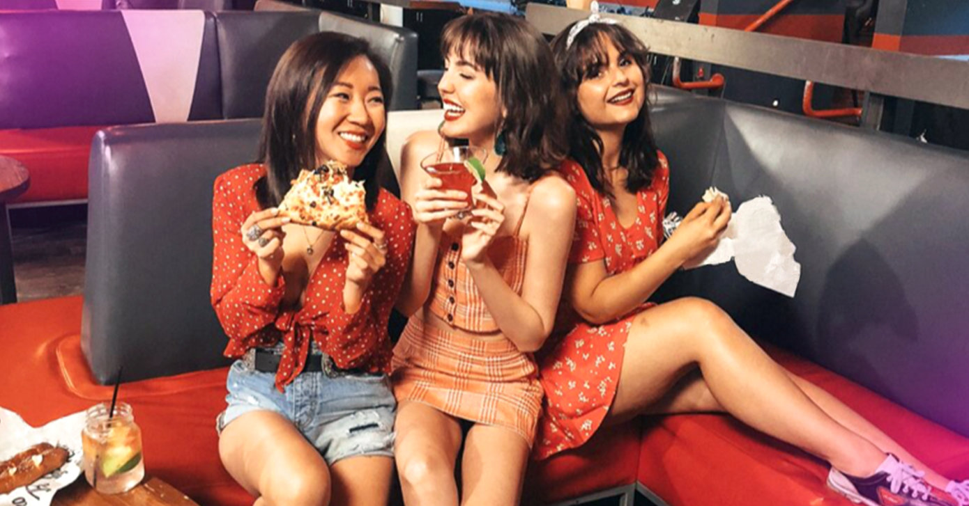 three girls eating on bench