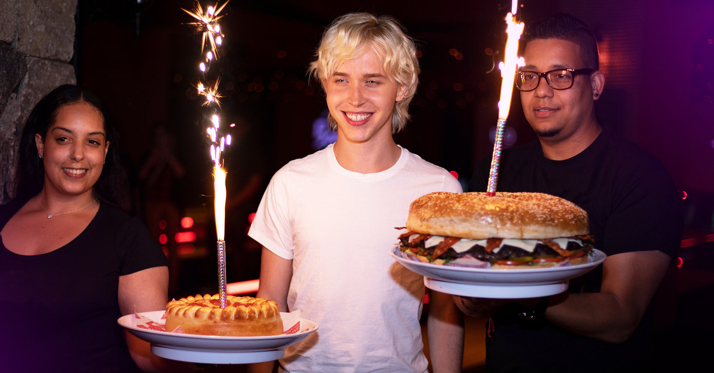 Boy in between two Bowlero servers, holding giant hamburger and pizza item with sparks coming out of them