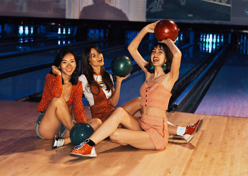 3 stylish teen girls posing on the lanes with bowling balls