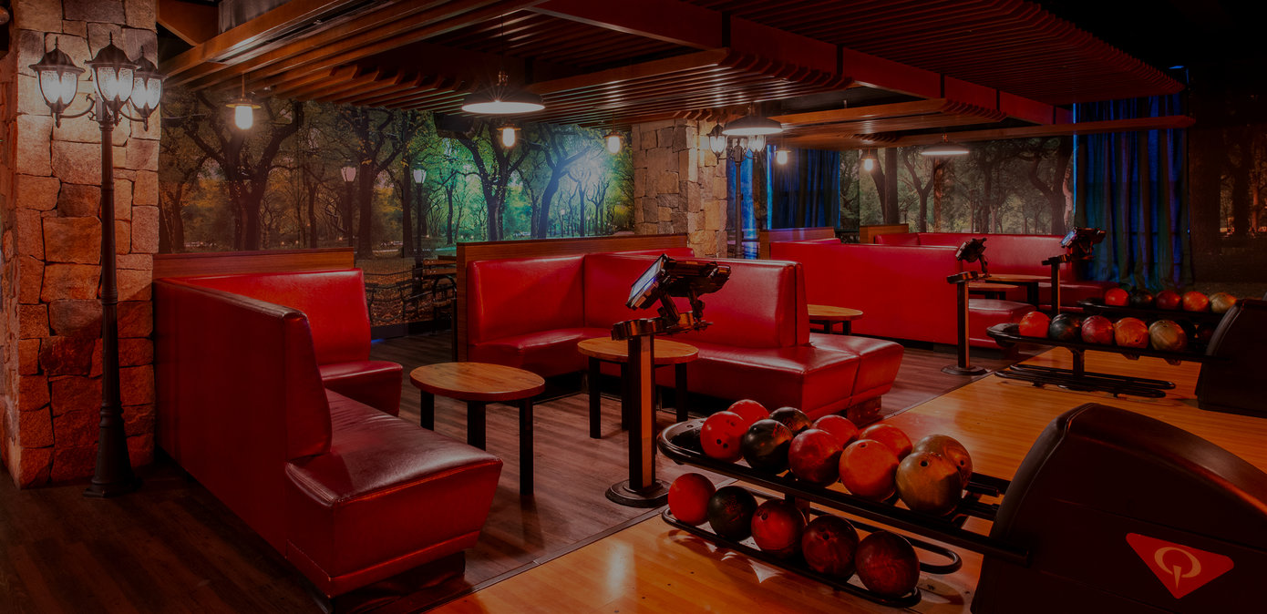 Central Park lanes. Red couches with tree mural on walls.