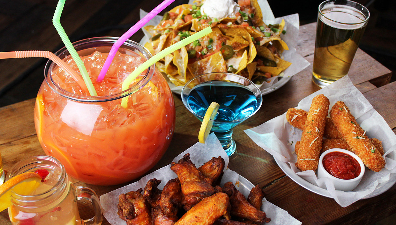 Drink in a fishbowl with colorful straws, nachos, chicken wings, mozzarella sticks, and three other drinks