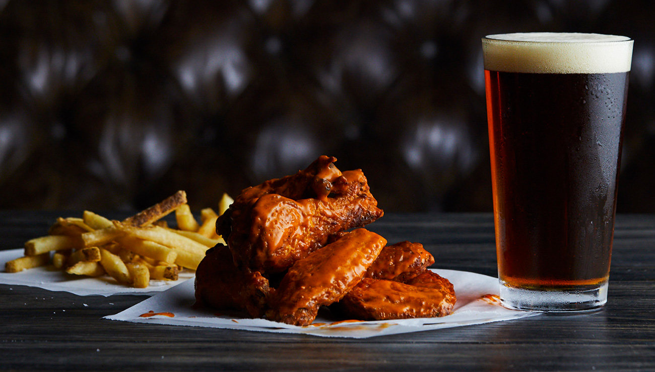 A pile of buffalo wings with fries on the left and a pint of beer on the right