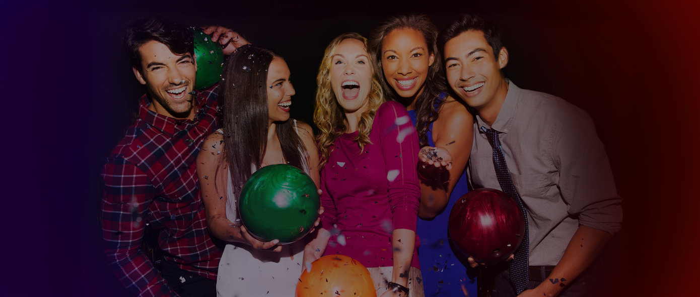 5 friends holding bowling balls and smiling with confetti raining down