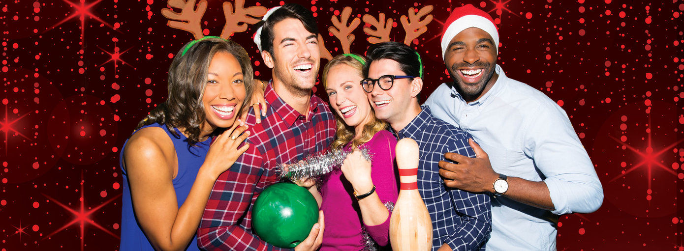 4 friends wearing Santa hats and reindeer ears holding bowling balls and pins