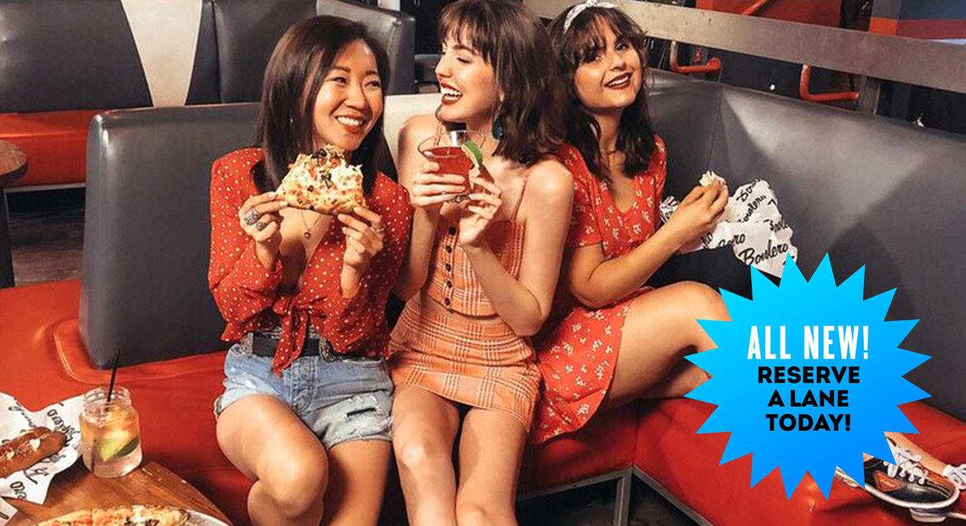three girls eating and drinking smiling at each other